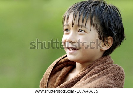 close up Portrait of happy joyful little boy smiling using towel after swimming - stock photo