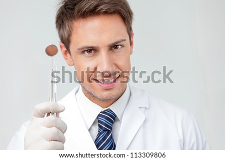 Close-up portrait of happy male dentist holding angled mirror and carver in clinic