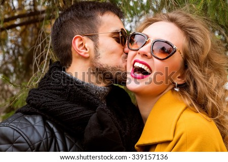 Close up portrait of happy smiling couple in love, guy kissing his girlfriend. Wearing bright outerwear, sunglasses. Outdoors lifestyle fashion portrait. Handsome brunet with beard and stunning blonde - stock photo