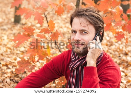 Close up portrait of happy smiling forty years old caucasian man talking on a mobile phone outdoor in an autumn park - stock photo