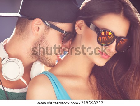 Close up portrait of happy smiling hipster couple in love. Wearing retro clothes and sunglasses. He kisses her on the neck, fashion. Vogue - stock photo