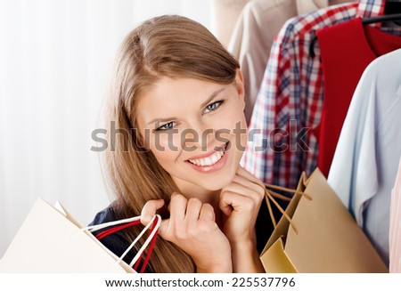 Close up portrait of happy woman buyer holding shopping bags in clothing store. Young beautiful female model happy with seasonal sales.   - stock photo