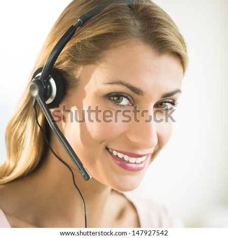 Close-up portrait of happy young female customer service representative wearing headset - stock photo