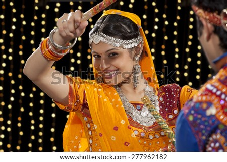 Close-up portrait of happy young woman performing Dandiya Raas with man against neon lights - stock photo