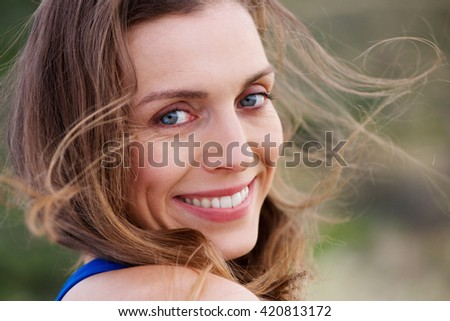 Close up portrait of healthy smiling woman outside - stock photo