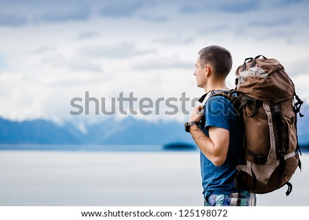 close up portrait of hiker looking at the horizon in the mountains - stock photo