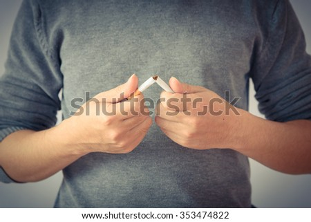 Close up portrait of human hands breaking down cigarette to pieces. Studio shot selective focus isolated on white background. Quit smoking addiction concept. Stop smoking message. Vintage look - stock photo