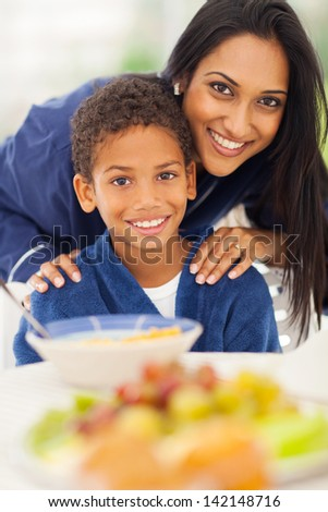 close up portrait of indian mother and son at breakfast table - stock photo
