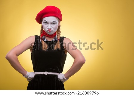 Close-up portrait of indignant female mime with white funny face, red hat and red scarf looking at the camera isolated on yellow background with copy place - stock photo