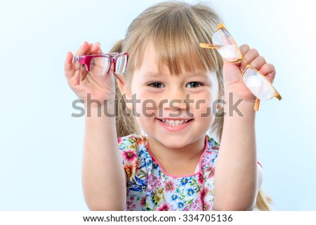 Close up portrait of infant holding two glasses at eye test.