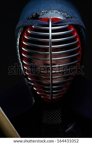 Close-up portrait of kendo fighter on the dark background - stock photo