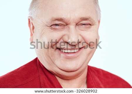 Close up portrait of laughing aged man wearing red shirt against white background - wellbeing concept - stock photo