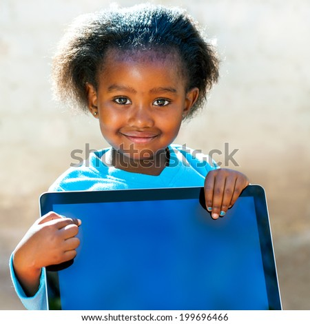 Close up portrait of little African girl pointing with finger at blank computer screen. - stock photo