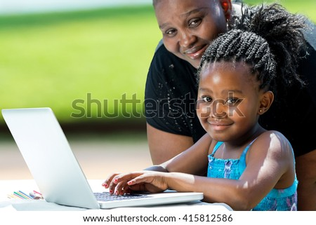 Close up portrait of little african girl with braids and mother with laptop.Kid typing on laptop against green background outdoors. - stock photo