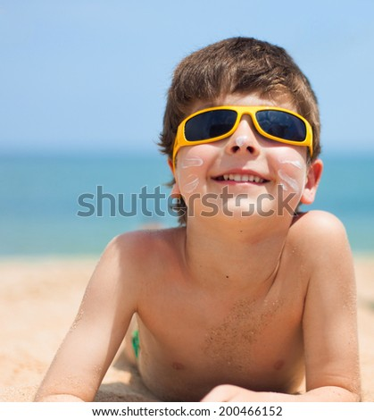 Close-up portrait of little boy on the beach - stock photo