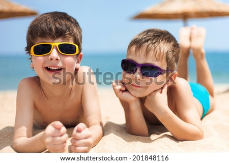 Close-up portrait of little boys on the beach - stock photo