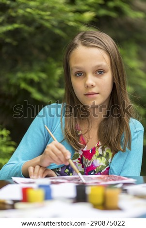 Close-up portrait of little cute girl draws paints. - stock photo