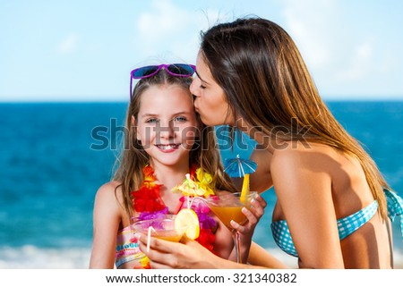 Close up portrait of little girl holding fruit cocktail on beach.Young Mother kissing girl on cheek. - stock photo