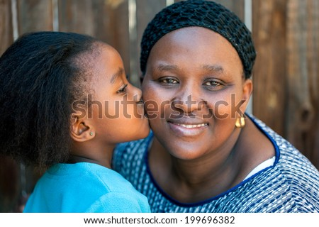 Close up portrait of little girl kissing mother on cheek outdoors. - stock photo