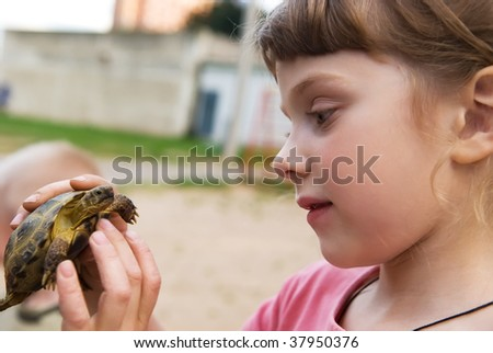 close up portrait of little girl playing with turtle outdoors - stock photo