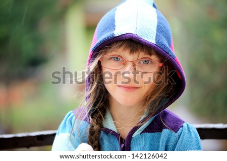 Close-up portrait of little girl wearing glasses and hoody - stock photo