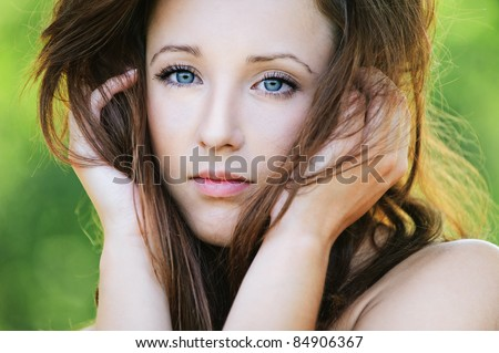 Close-up portrait of lovely dark-haired young woman holding her head in hands at summer green park.