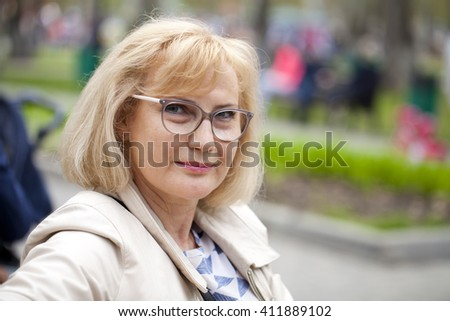 Close up portrait of lovely middle aged woman in the summer park  - stock photo