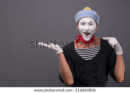 Close-up portrait of male mime with grey hat and white face funny smiling to the camera and showing with finger on his left hand isolated on grey background - stock photo
