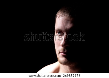 Close-up portrait of man on a black background - stock photo