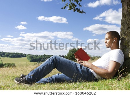 Close up Portrait of man reading a book underneath the shade of a tree on a sunny day - stock photo