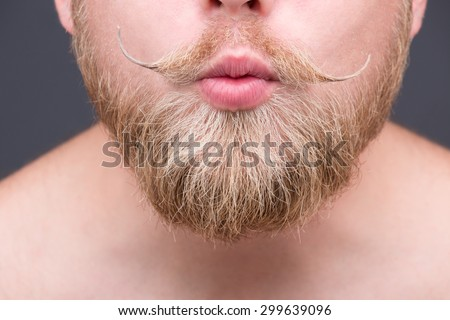 Close-up portrait of man's beard. Mature man shutting lips and demonstrating his pleasure to someone isolated on grey.