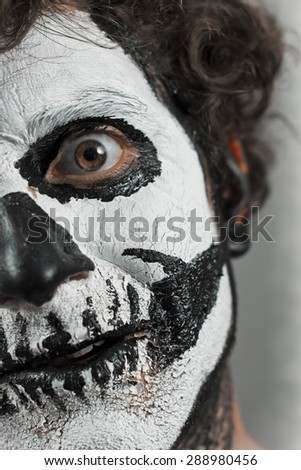 Close up portrait of man with halloween skull face paint - stock photo