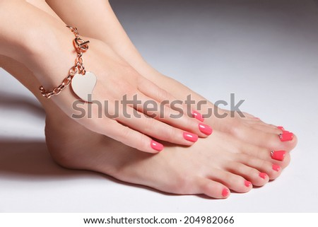 Close-up portrait of manicured nails and pedicured toes with gel - stock photo