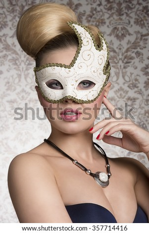 close-up portrait of masquerade pretty blonde girl with elegant hair-style and necklace and cute decorated white mask. Looking in camera - stock photo