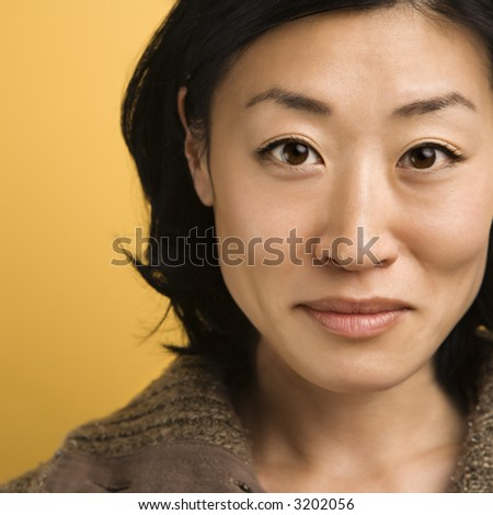 Close up portrait of mid adult Asian woman. - stock photo