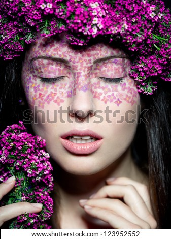 Close up portrait of model with flowered wreath and fashion make up with eyes closed
