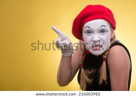 Close-up portrait of playful female mime with white face, red hat and red scarf looking at the camera and showing with her finger aside isolated on yellow background with copy place