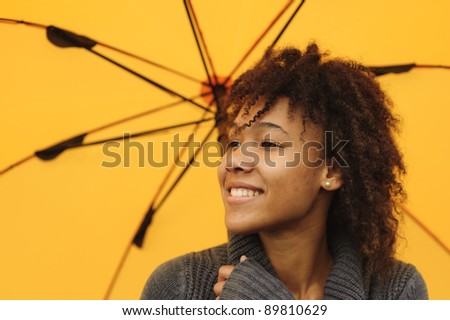 Close up portrait of pretty African American girl with yellow umbrella - stock photo