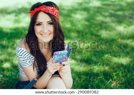 Close-up portrait of pretty brunette girl, sitting on the grass with mobile phone. Wearing red bandana and striped top. Sunny day. Copy space. - stock photo