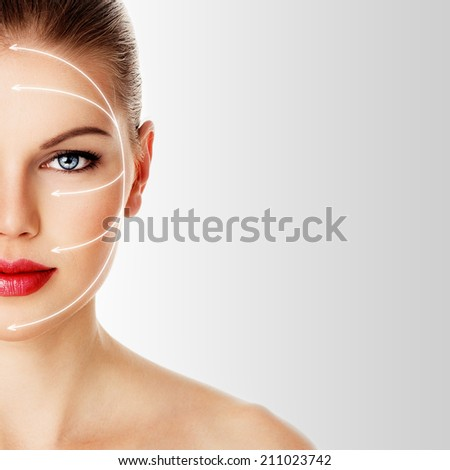Close-up portrait of pretty woman ready for rejuvenation treatment. Young attractive blue eyed female with arrows for plastic surgery on her face.  - stock photo