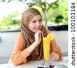 Close-up portrait of pretty young Asian Muslim woman at cafe drink orange juice - stock photo