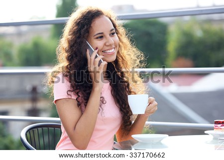 Close up portrait of pretty young woman speaking by cellphone and drinking coffee - stock photo