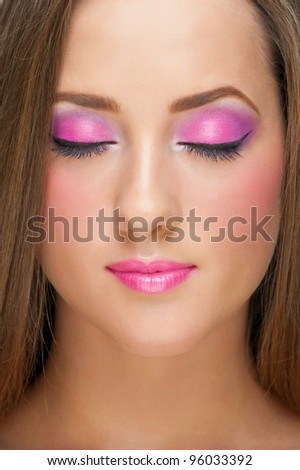 Close-up portrait of pretty young woman with bright stylish make-up with closed eyes