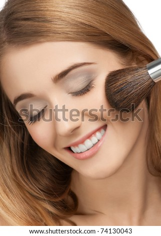 Close-up portrait of pretty young woman with brush for makeup with closed eyes, isolated on white - stock photo