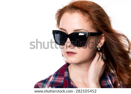 Close-up portrait of red-haired girl with sunglasses looking to the side. Woman in plaid shirt isolated on a white background