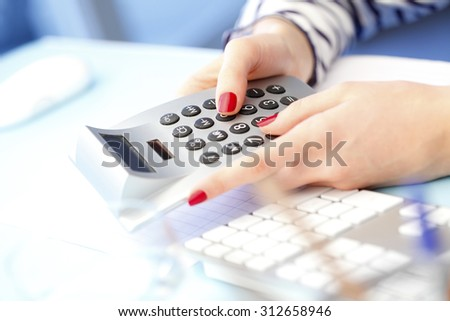 Close-up portrait of red nails businesswoman hand while using calculator.  - stock photo