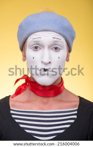 Close-up portrait of sad mime with white face,  grey hat and red scarf looking at the camera isolated on yellow background - stock photo