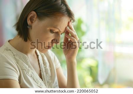 Close-up portrait  of sad woman have a headache - stock photo