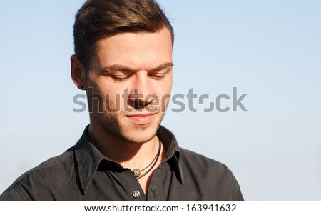 close-up portrait of sad young man looking down clean blue sky on background - stock photo