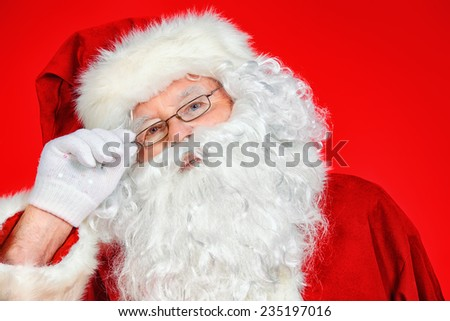 Close-up portrait of Santa Claus. Christmas time. Red background. - stock photo
